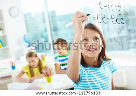 Portrait of lovely girl doing sums on transparent board with two schoolmates on background - stock photo