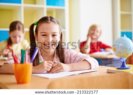 Portrait of lovely girl looking at camera at lesson of drawing - stock photo