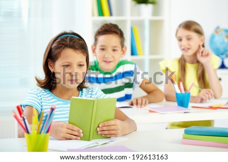 Portrait of lovely girl looking in notepad with her two schoolmates on background - stock photo