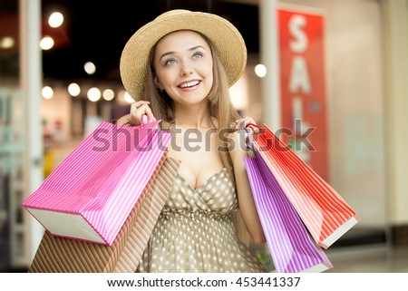 Portrait of lovely happy fashion woman wearing hat and dress standing in shopping centre smiling looking sideways and holding colorful shopping bags in both hands. Red sale sign on background - stock photo