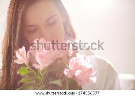 Portrait of lovely lady looking at flowers and smelling them - stock photo