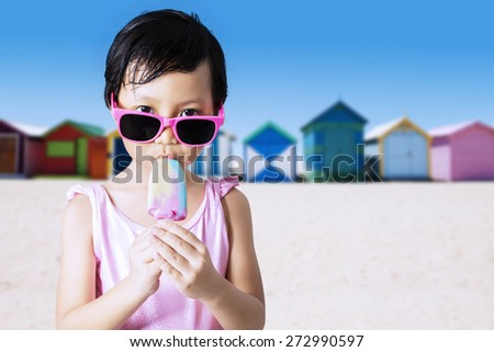 Portrait of lovely little kid wearing sunglasses and swimsuit on the beach while enjoy ice cream - stock photo