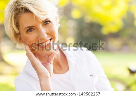 portrait of lovely middle aged woman sitting at the park  - stock photo