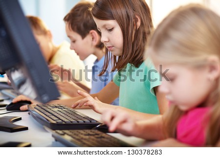 Portrait of lovely schoolgirl looking at computer keyboard while typing - stock photo