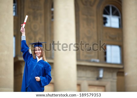 Portrait of lovely student with graduation certificate looking at camera - stock photo