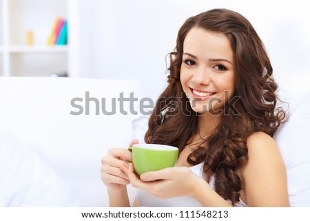 Portrait of lovely young woman having cup of tea at home - stock photo