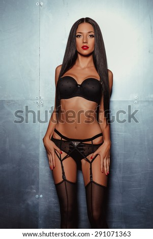 portrait of lovely young woman in black lingerie posing against steel wall - stock photo