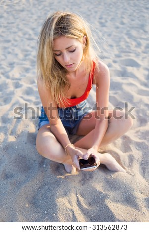 Portrait of lovely young woman sending text message with mobile phone while sitting on the beach, charming hipster girl chatting on cell phone outdoors in summer day resting after strolling - stock photo