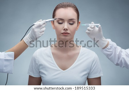 portrait of lovely young woman with closed eyes getting permanent makeup and injection  - stock photo