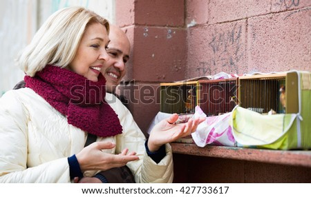 Portrait of loving cheerful mature couple feeding birds in cage outdoors - stock photo