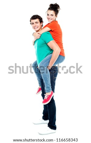 Portrait of loving couple enjoying together while piggyback ride - stock photo