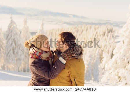 portrait of loving couple in snowy mountains - stock photo