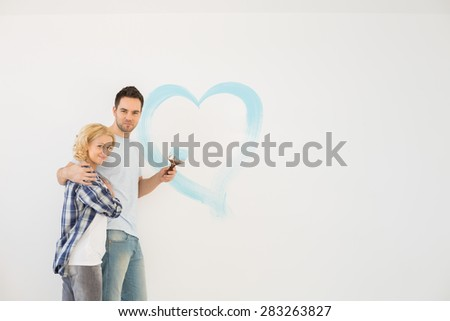 Portrait of loving mid-adult couple with painted heart on wall - stock photo