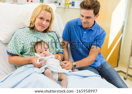 Portrait of loving mid adult woman with newborn baby girl sitting by man in hospital room - stock photo
