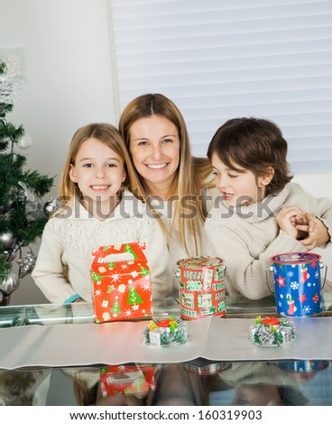 Portrait of loving mother and siblings with Christmas presents at home - stock photo