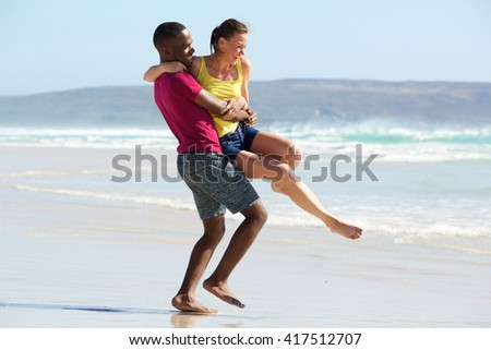 Portrait of loving young couple having fun outdoors on the beach - stock photo