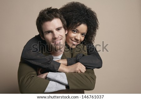 Portrait of loving young couple smiling on colored background - stock photo