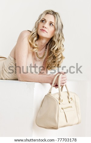 portrait of lying woman wearing summer clothes with a handbag - stock photo