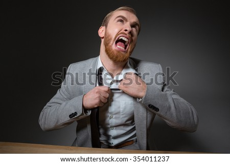 Portrait of mad screaming businessmen with beard in grey suit over grey background - stock photo