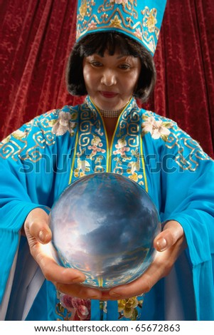 Portrait of magician holding crystal ball - stock photo