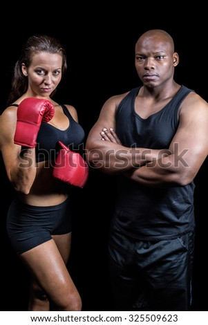 Portrait of male and female athletes standing against black background - stock photo
