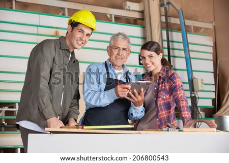 Portrait of male and female carpenters with digital tablet in workshop - stock photo