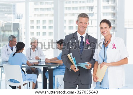 Portrait of male and female doctors with medical reports against pink breast cancer awareness ribbon - stock photo