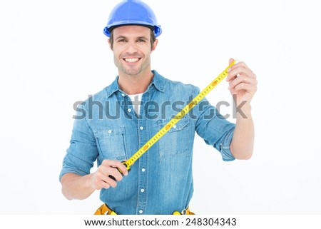 Portrait of male architect holding tape measure over white background - stock photo