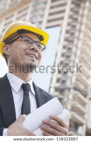Portrait of male architect on construction site carrying blueprints - stock photo