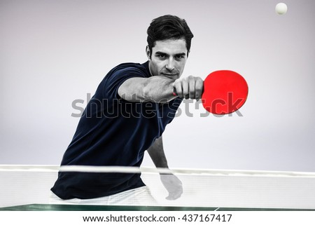 Portrait of male athlete playing table tennis against grey background - stock photo