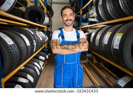 Portrait of  male auto mechanic in tire store - stock photo