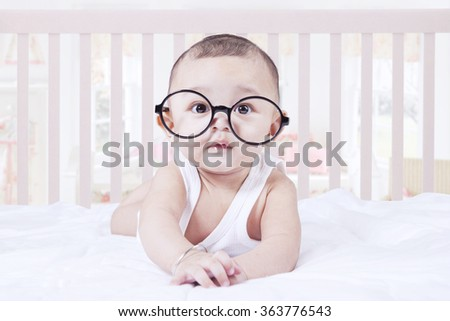 Portrait of male baby boy lying on the bedroom while wearing glasses and looking at the camera - stock photo