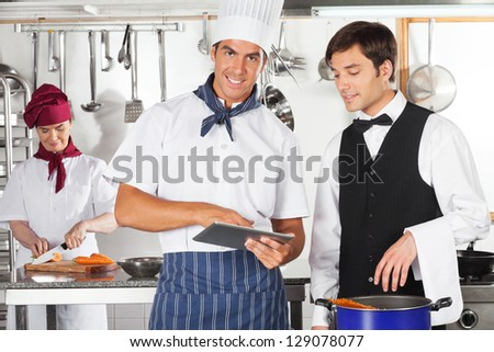 Portrait of male chef with waiter using digital tablet in commercial kitchen - stock photo