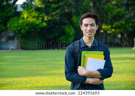 portrait of male college student holding book at campus - stock photo