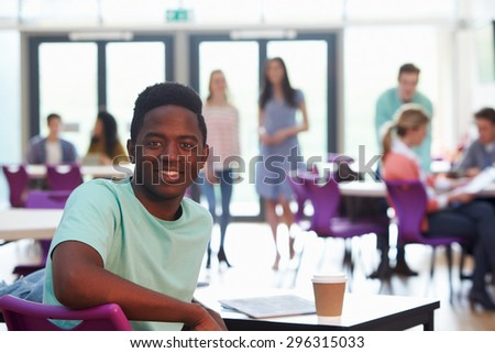 Portrait Of Male College Student Relaxing In Cafeteria - stock photo