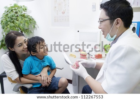 Portrait of male dentist show a sample of braces to his patient at office - stock photo