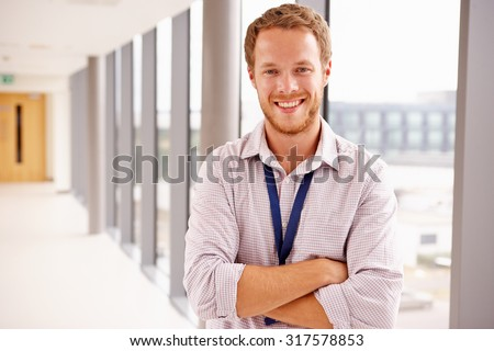 Portrait Of Male Doctor Standing In Hospital Corridor - stock photo
