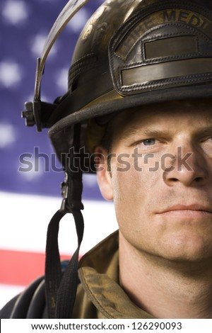 Portrait of male firefighter against American flag - stock photo