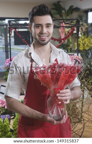 Portrait of male florist holding dried red flowers in shop - stock photo