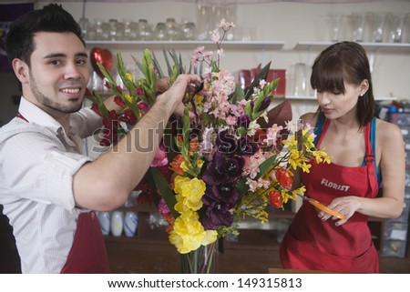 Portrait of male florist working with female colleague in flower shop - stock photo
