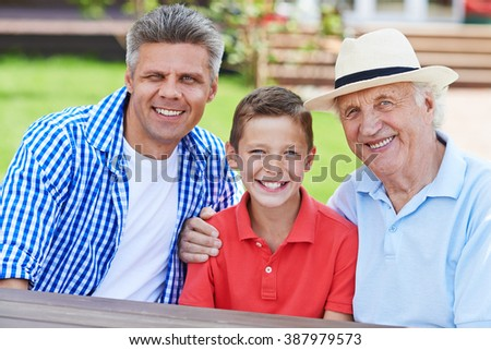 Portrait of male generations sitting together and smiling - stock photo