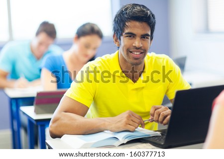 portrait of male indian university student in lecture room - stock photo