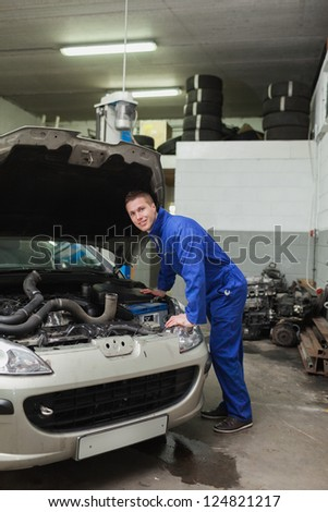 Portrait of male mechanic examining car engine in workshop - stock photo