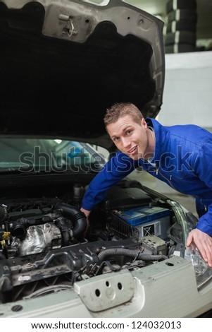 Portrait of male mechanic working under bonnet of car - stock photo