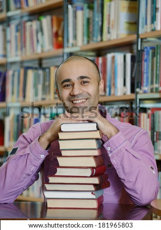 Portrait of male middle eastern student sitting at desk in Bergen city library with a pile of books and looking at camera - stock photo