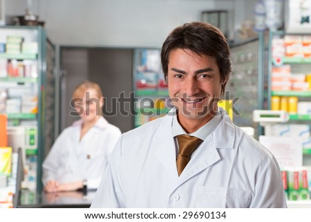 portrait of male pharmacist looking at camera and smiling - stock photo