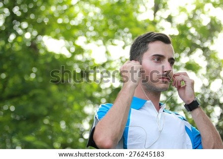portrait of male runner adjusting his earphone during jogging with copy space - stock photo