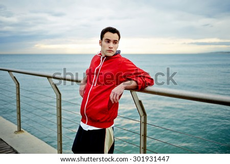 Portrait of male runner taking break after run while standing on a pier enjoying beautiful sea landscape view, sporty young man resting after active physical training outdoors, jogger taking break - stock photo