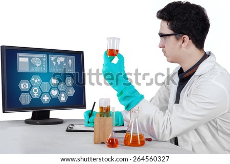 Portrait of male scientist with protective gloves and goggles doing experiment - stock photo