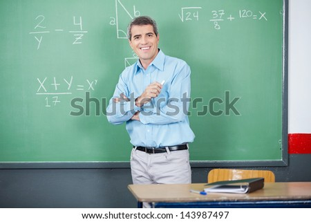 Portrait of male teacher standing arms crossed against board in classroom - stock photo